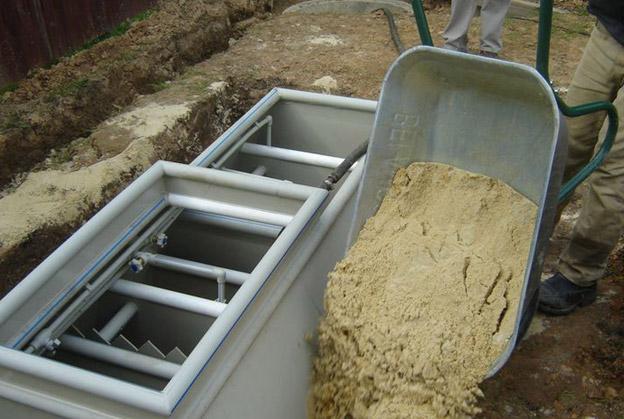 Фото: завершающий этап монтажа - обратная засыпка септика в котловане